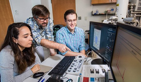 Dr Nate Magee (center) with students Katie Boaggio and Lucas Bancroft work with their Hitachi-Quorum cryo-SEM at TCNJ.